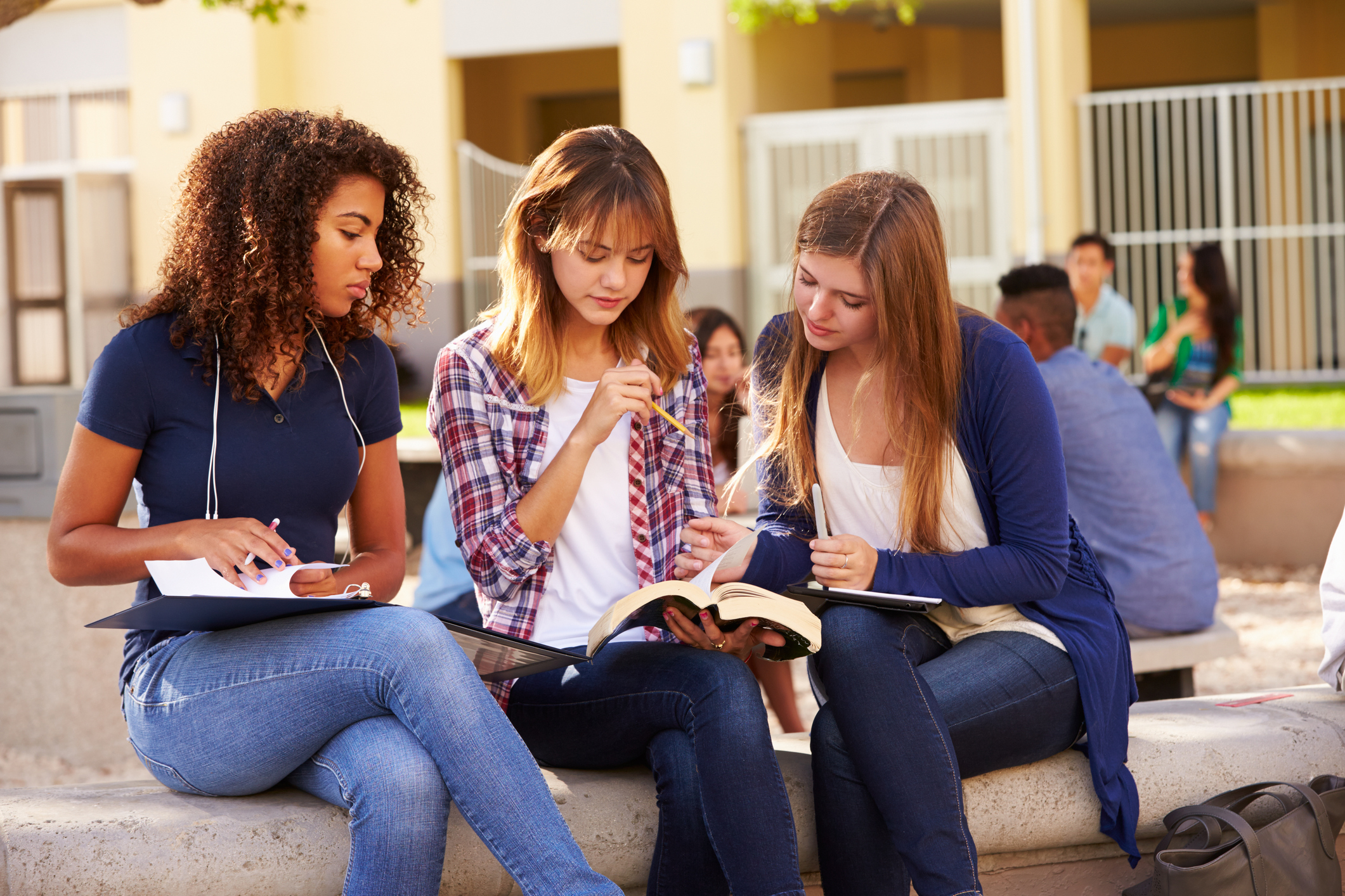 Three Female High School Students Working On Campus With Text Books And File